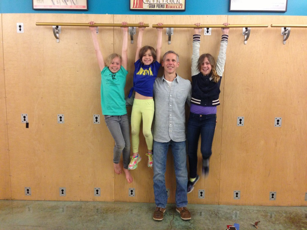 Ben Gordon with his kids hanging from Castle Hill ballet barres