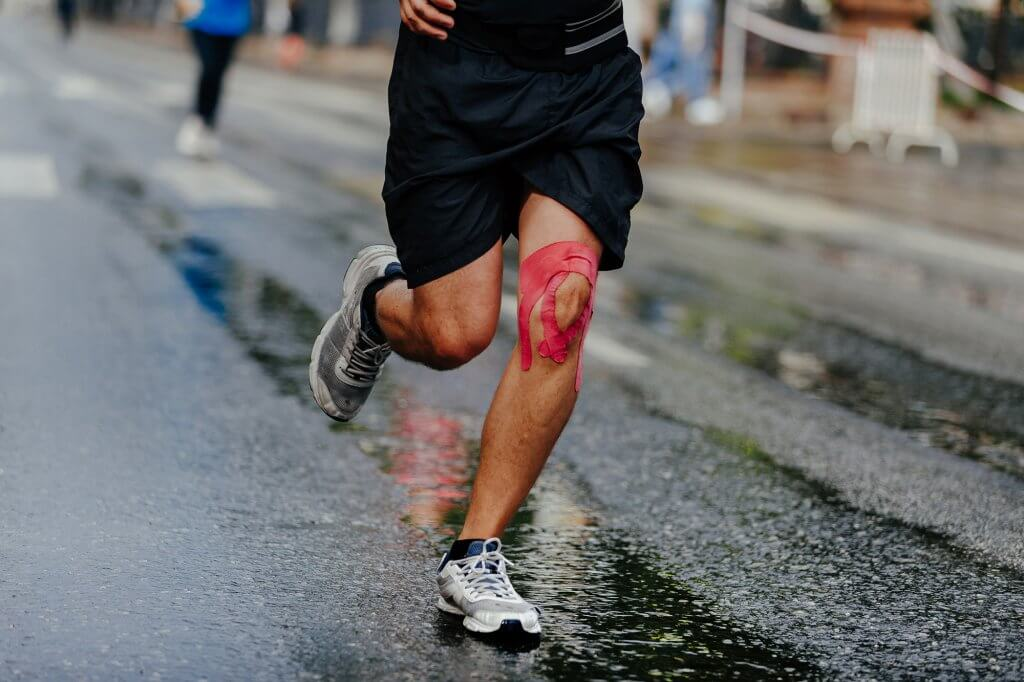 Man with Kinesiotape on Knee Running