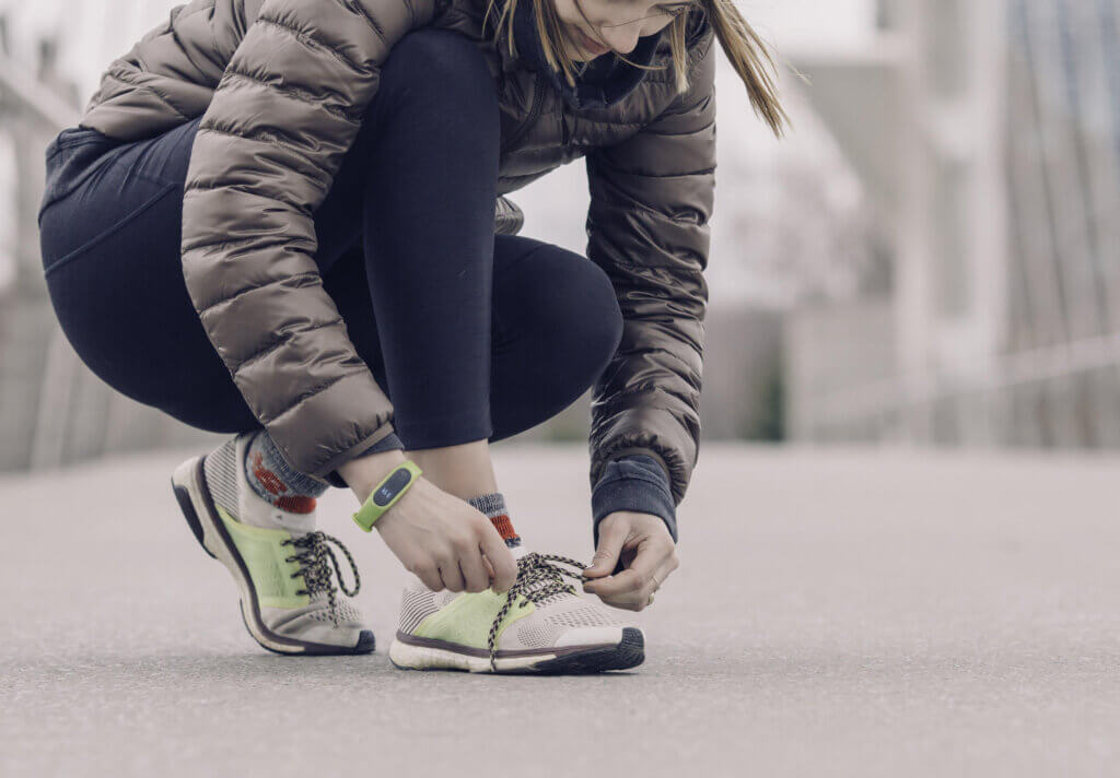 Woman Athlete Tying Shoes in Winter in Health Coach Holiday Survival Guide Blog Banner